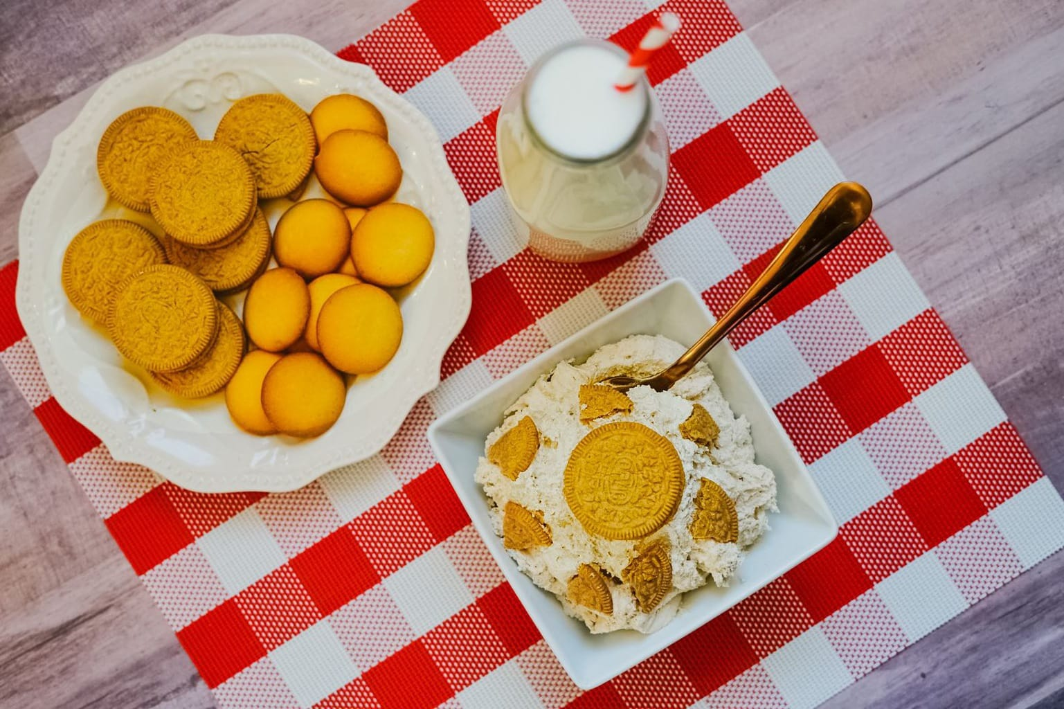 picture of cheesecake dip with carrot cake Oreos and milk on a checkered tablecloth